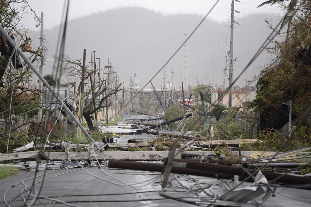 Electricity poles and lines lay toppled on the road after Hurricane Maria hit the eastern region of the island, in Humacao, Puerto Rico, Wednesday, Sept. 20, 2017. The strongest hurricane to hit Puerto Rico in more than 80 years destroyed hundreds of homes, knocked out power across the entire island and turned some streets into raging rivers in an onslaught that could plunge the U.S. territory deeper into financial crisis.