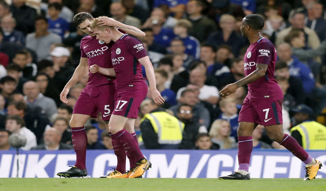 Manchester City's scorer Kevin De Bruyne, 2nd left, and his teammates John Stones, left, and Raheem Sterling, right, celebrate the opening goal during their English Premier League  match against Chelsea at Stamford Bridge stadium in London, Saturday, Sept. 30, 2017.