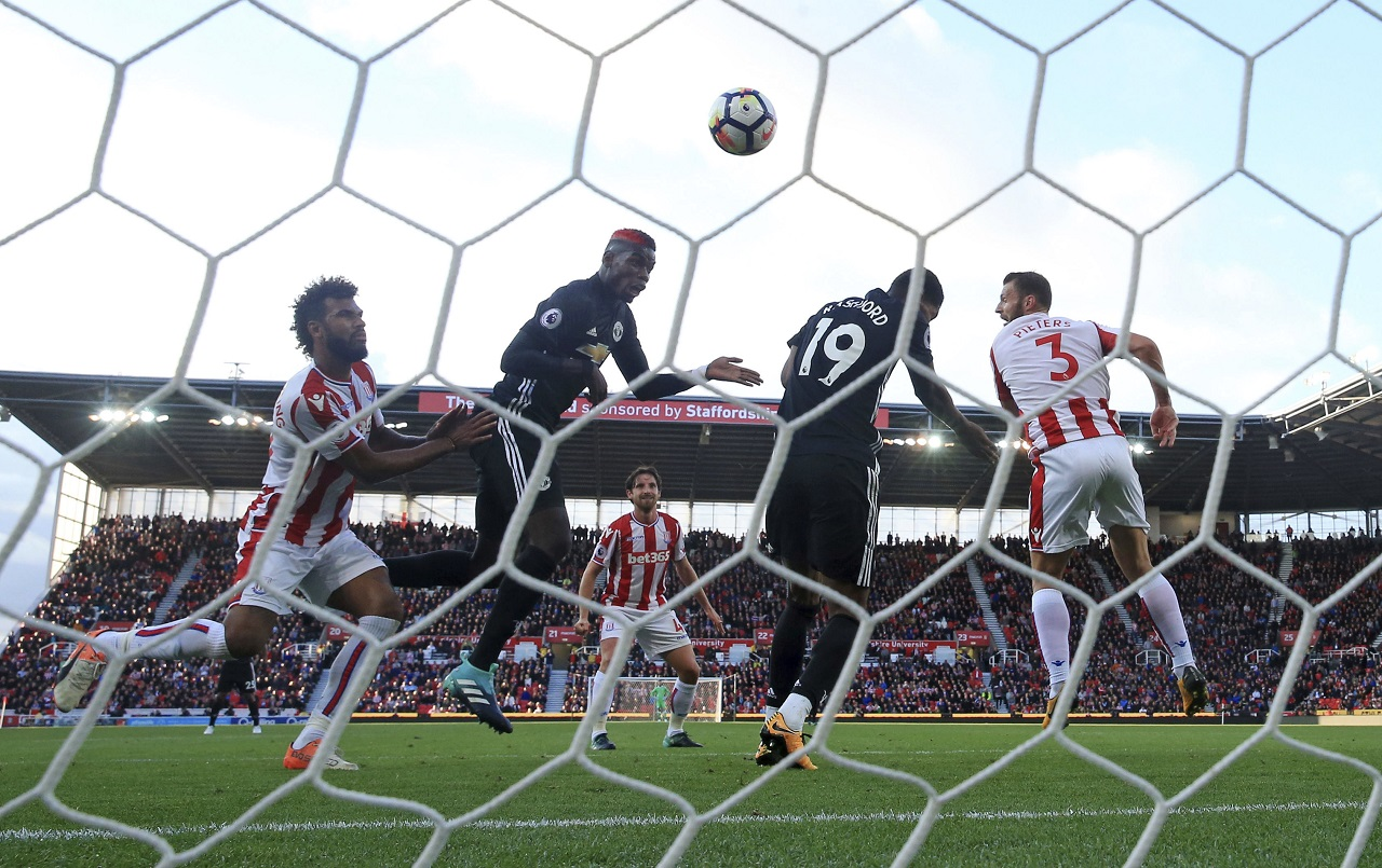 Manchester United's Marcus Rashford, centre right, scores his side's first goal of the game against Stoke City following a header from team mate Paul Pogba, second left, during their English Premier Leaguefootball match at the bet365 Stadium, Stoke, England, Saturday, Sept. 9, 2017.