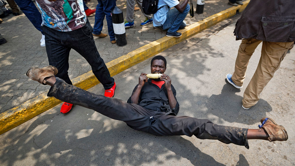 A supporter of opposition leader Raila Odinga eats a cob or corn and does the splits as he celebrates after hearing the verdict, on a street opposite the Supreme Court in downtown Nairobi, Kenya, Friday, Sept. 1, 2017. Kenya's Supreme Court on Friday nullified President Uhuru Kenyatta's election win last month and called for new elections within 60 days, shocking a country that had been braced for further protests by opposition supporters.