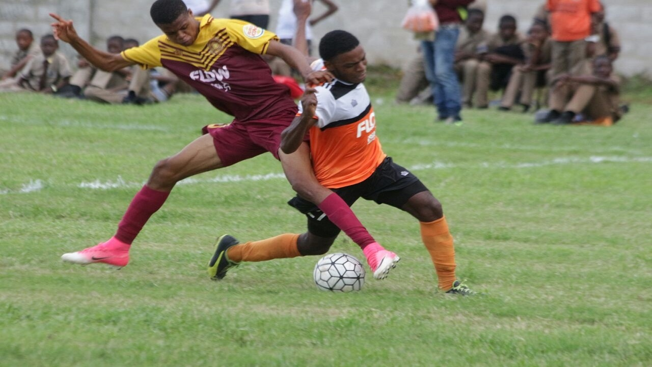 A player from Wolmer's (left) battles his Tivoli Gardens counterpart for the ball in their Manning Cup encounter at Tivoli on Monday. (PHOTOS: Marlon Reid)