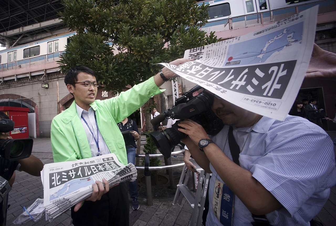 A man distributes an extra edition of a newspaper reporting about North Korea's missile launch, at Shimbashi Station in Tokyo, Friday, Sept. 15, 2017.