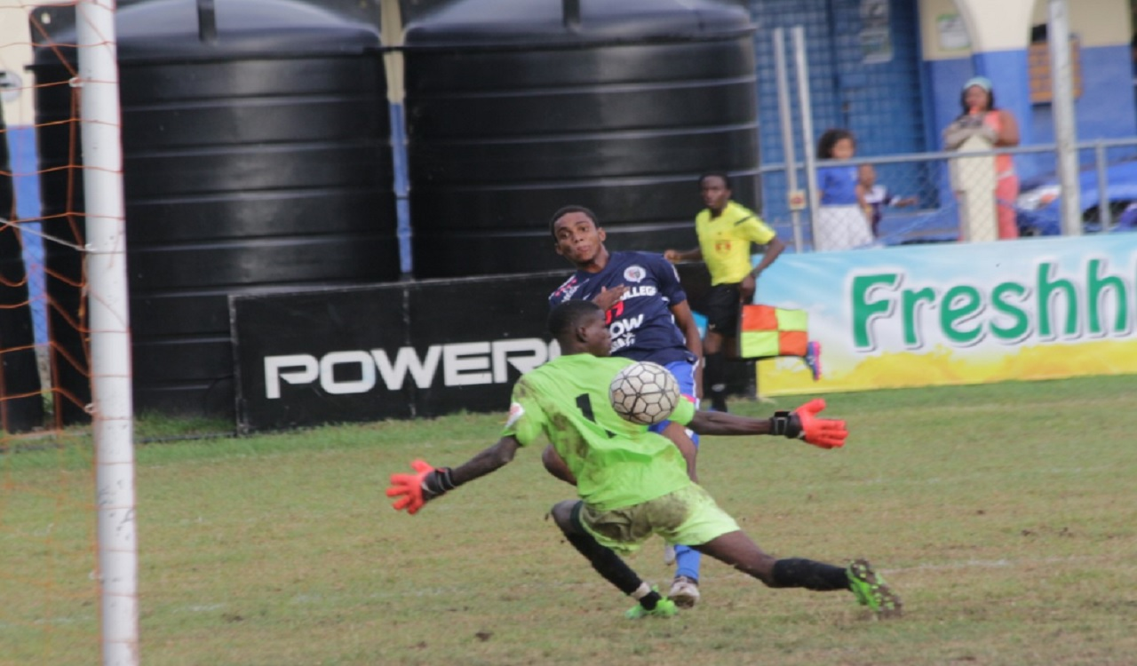 Jamaica College's (JC) Shaniel Thomas scores against goalkeeper Jean-Luke Wilmot of Mona  High during their Group B return leg match of the ISSA/FLOW Manning Cup competition at JC on Tuesday.