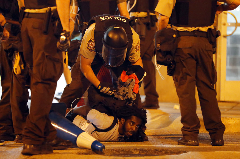 Police arrest a man as demonstrators march in response to a not guilty verdict in the trial of former St. Louis police officer Jason Stockley, Sunday, Sept. 17, 2017, in St. Louis. Stockley was acquitted in the 2011 killing of a black man following a high-speed chase. (AP Photo/Jeff Roberson)