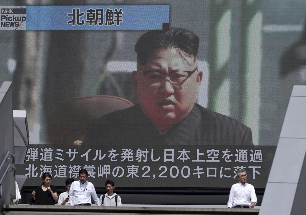 People walk past a public TV screen showing a file footage of North Korean leader Kim Jong Un during news on North's missile launch, in Tokyo, Friday, Sept. 15, 2017.