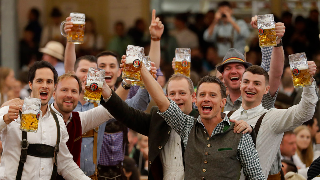 Young men celebrate the opening of the 184th Oktoberfest beer festival in the 'Paulaner brewery' tent in Munich, Germany, Saturday, Sept. 16, 2017. The world's largest beer festival will be held from Sept. 16 until Oct. 3.