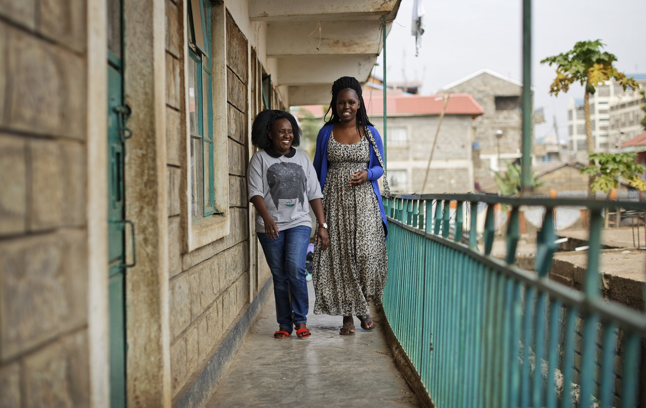 In this photo taken Wednesday, Aug. 23, 2017, Sheila Kariuki, left, an ethnic Kikuyu, and her friend Lucy Anyango, right, an ethnic Luo, walk together outside Lucy's apartment in the Lucky Summer neighbourhood of Nairobi, Kenya.