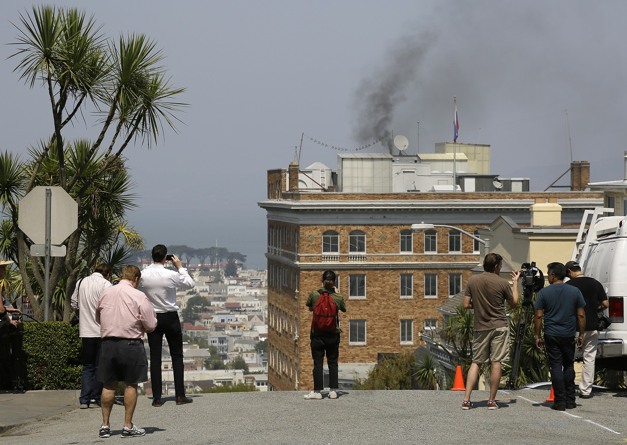 People stop to watch black smoke coming from the roof of the Consulate-General of Russia Friday, Sept. 1, 2017, in San Francisco. The San Francisco Fire Department says acrid, black smoke seen pouring from a chimney at the Russian consulate in San Francisco was apparently from a fire burning in a fireplace.