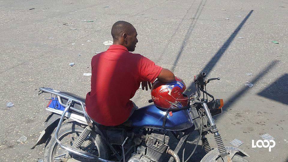 Un chauffeur observant une pause, sur sa motocyclette.