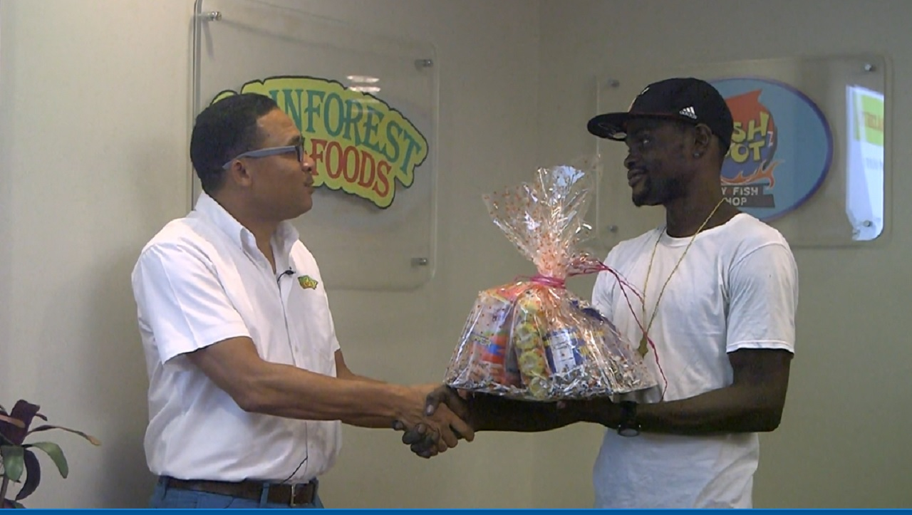 Rainforest Seafoods marketing manager, Roger Lyn (left) hands over a gift basket to Alphanso Coombs.