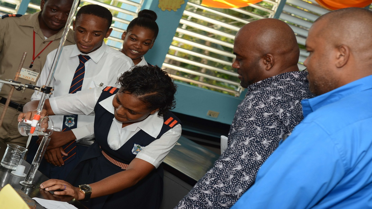 Students at the St Mary Technical High School demonstrate an experiment to the Minister of Science, Energy and Technology Dr. Andrew Wheatley, Mayor of Port Maria Richard Creary during the opening of the new chemistry lab.