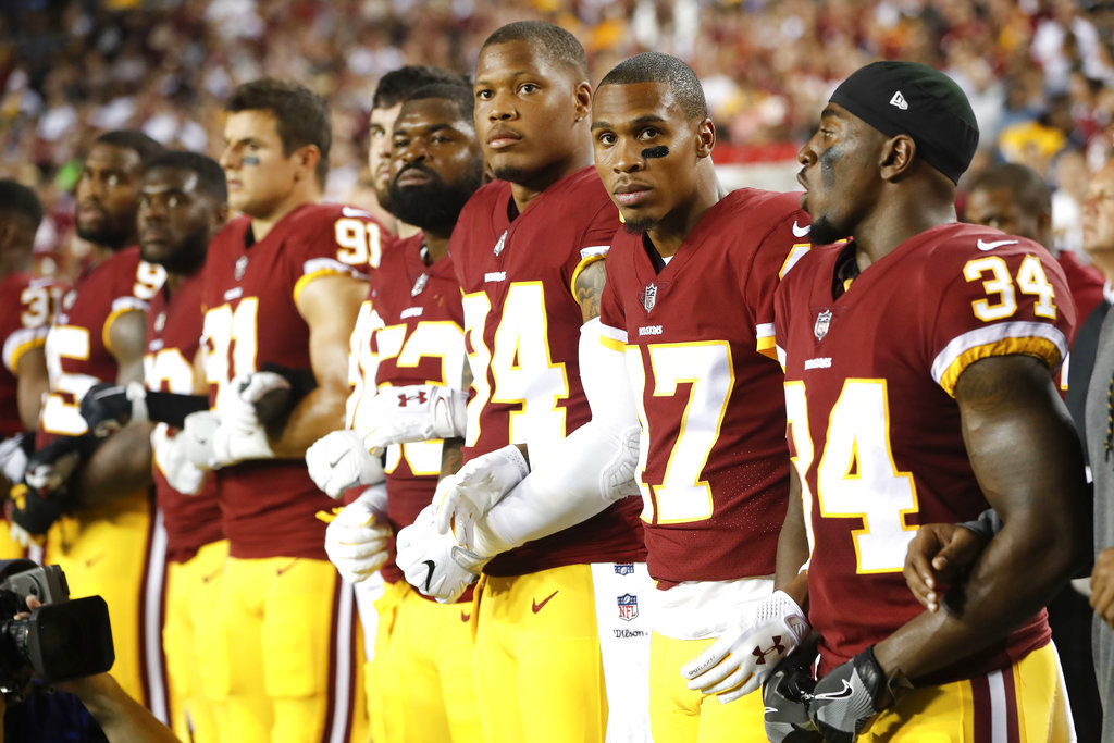 Member of the Washington Redskins stand arm in arm during the playing of the National Anthem before an NFL football game against the Oakland Raiders in Landover, Md., Sunday, Sept. 24, 2017. (AP Photo/Pablo Martinez Monsivais)