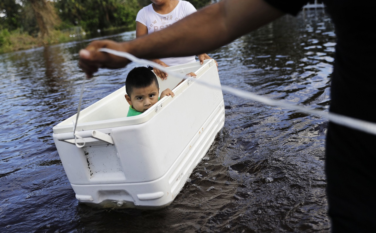 lfonso Jose Jr., 2, is floated down his flooded street by his parents as the wade through water to reach an open convenience store in the wake of Hurricane Irma in Bonita Springs, Fla., Tuesday, Sept. 12, 2017.
