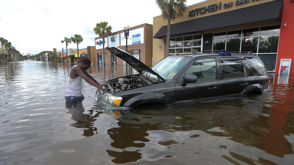 John Duke tries to figure out how to salvage his flooded vehicle in the wake Hurricane Irma, Monday, Sept. 11, 2017, in Jacksonville, Florida