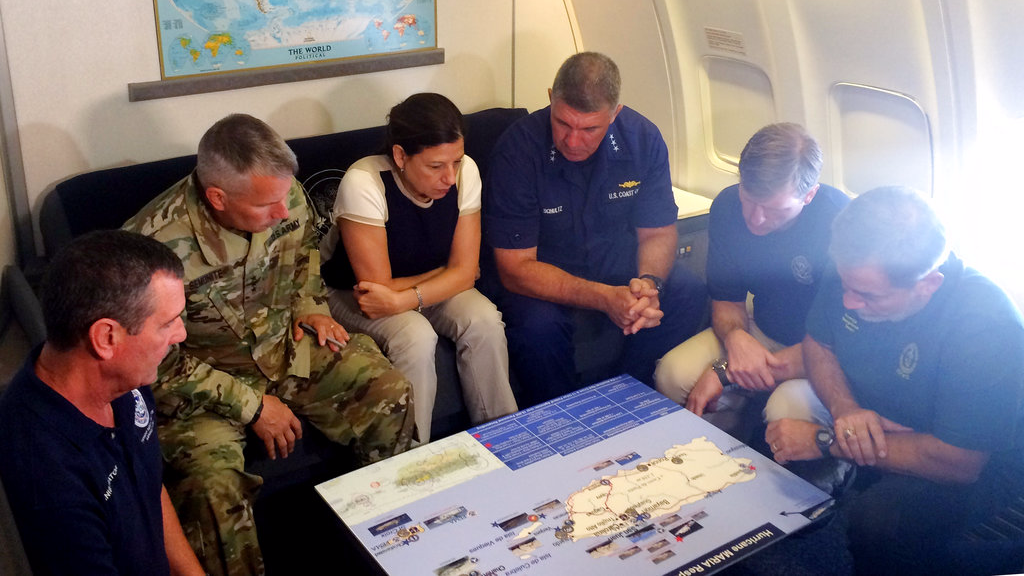 Acting Homeland Secretary Elaine Duke, center, is briefed on the Hurricane Maria response during a flight to Puerto Rico on Friday, Sept. 29, 2017. President Donald Trump on Thursday cleared the way for more supplies to head to Puerto Rico by waiving restrictions on foreign ships delivering cargo to the island.
