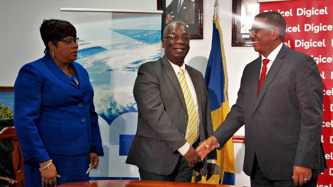 Chief Executive Officer of Digicel Barbados, Alex Tasker (right), congratulates Minister of Education, Ronald Jones as Chief Education Officer, Karen Best looks on.