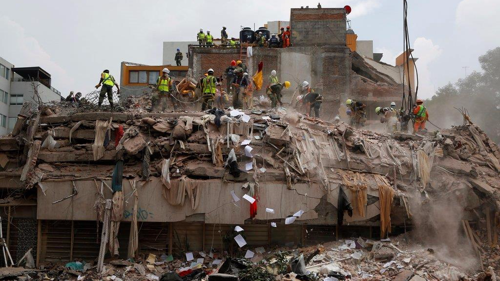 Workers shovel papers and debris off the top of the rubble of a building that collapsed in last week's 7.1 magnitude earthquake, at the corner of Gabriel Mancera and Escocia streets in the Del Valle neighborhood of Mexico City, Monday, Sept. 25, 2017. Search teams were still digging through dangerous piles of rubble Monday, hoping against the odds to find survivors after the Sept. 19 quake.(AP Photo/Rebecca Blackwell)