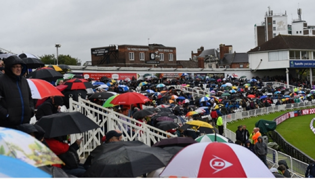 Supporters seek shelter under umbrellas at Trent Bridge.