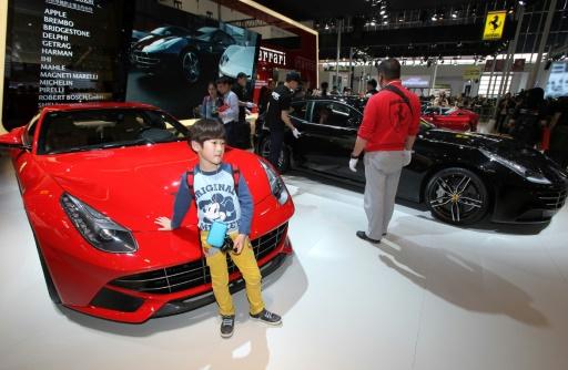 Un enfant prend la pose devant une Ferrari au salon auto de Pekin