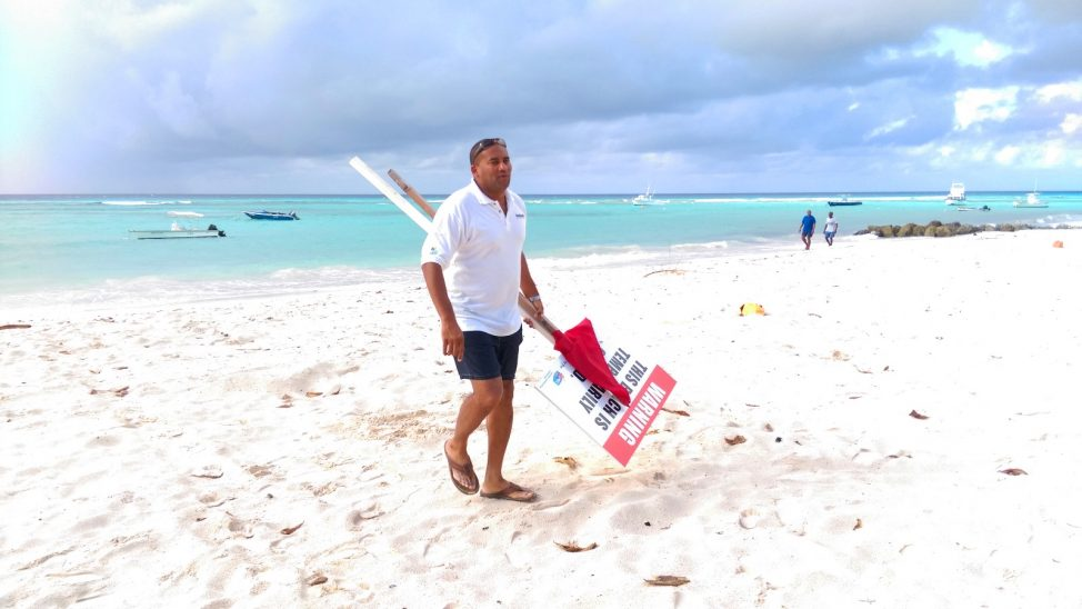 After a quick sea bath at Worthing Beach in December 2016, Minister of Tourism and International Transport, Richard Sealy, removed the signs which declared the beach closed. (J.Weekes/BGIS)