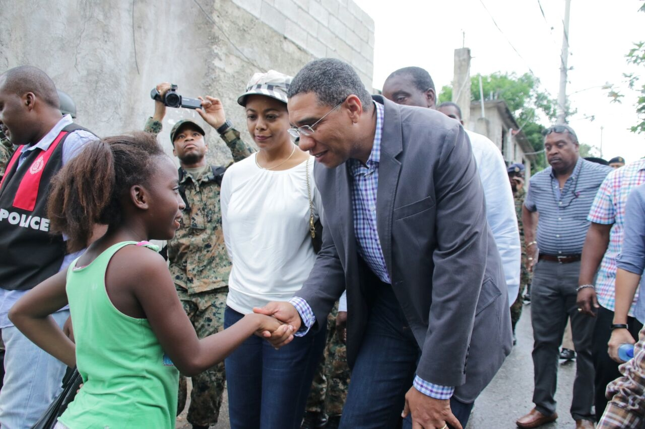 Prime Minister Andrew Holness greets a girl in Mt Salem, St James during a tour of the area, which was declared the first Zone of Special Operations.