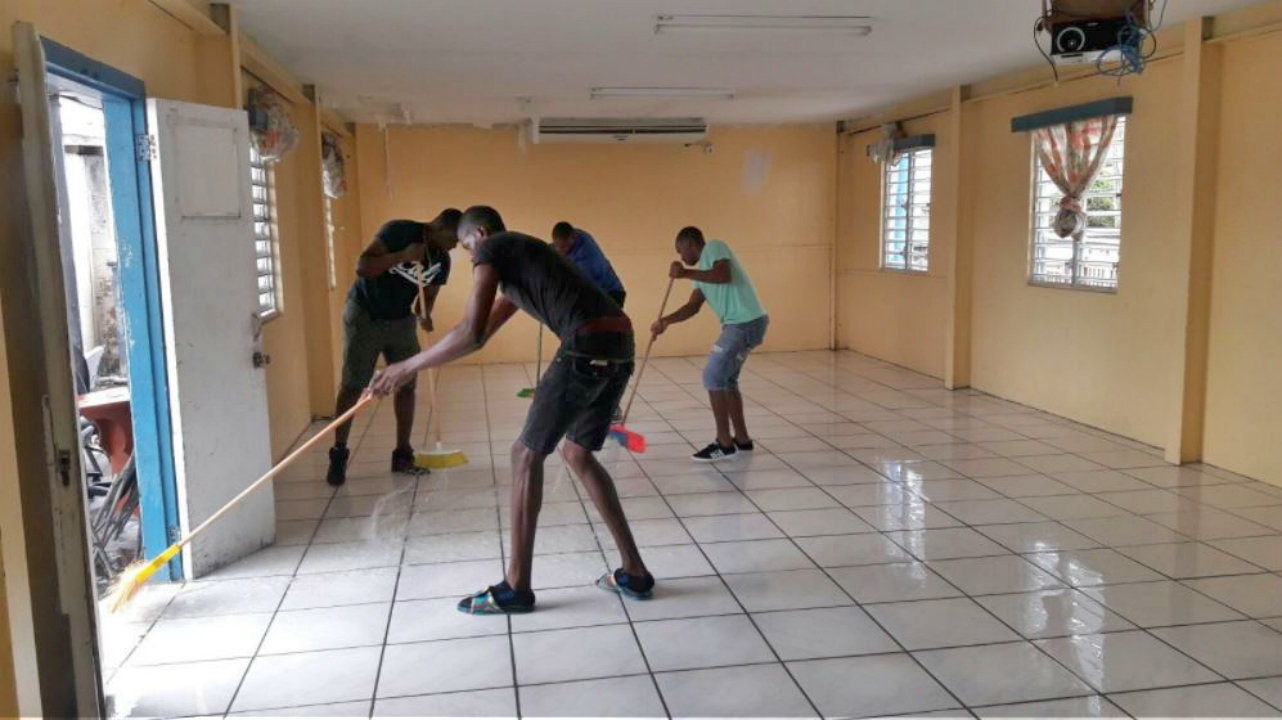 Police recruits mopping up and starting the cleanup at their headquarters. (PHOTO: Twitter|@pmharrisskn)