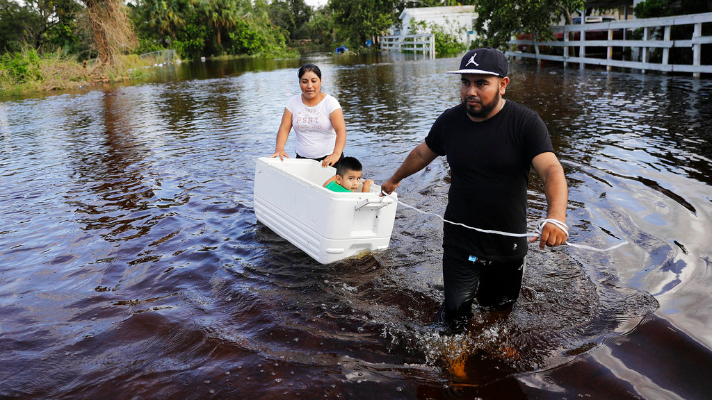 Alfonso Jose pulls his son Alfonso Jr., 2, in a cooler with his wife Cristina Ventura as they wade through their flooded street to reach an open convenience store in the wake of Hurricane Irma in Bonita Springs, Fla., Tuesday, Sept. 12, 2017. (AP Photo/David Goldman)