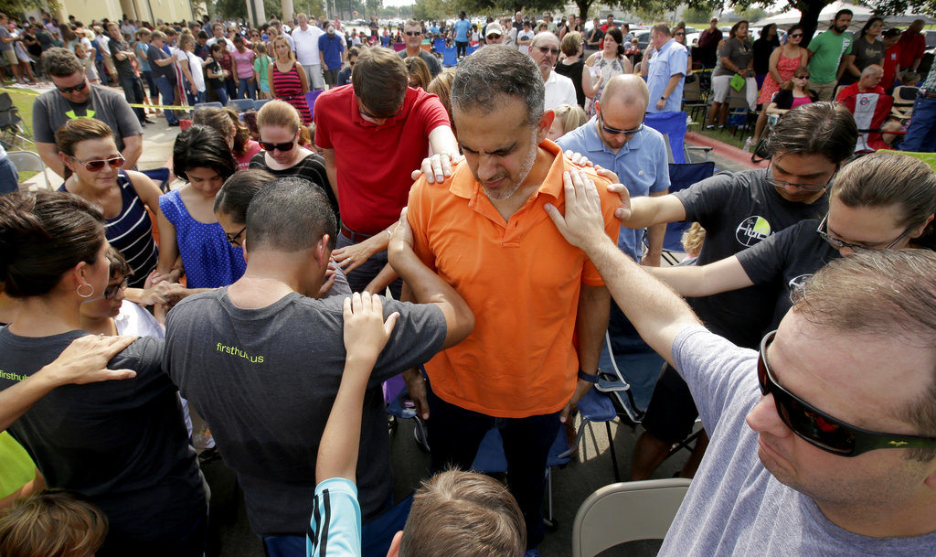 Church members gather to pray around flood victim Carlos Ochoa during Sunday service in the parking lot of the First Baptist Church Sunday, Sept. 3, 2017, in Humble, Texas. The church building was flooded with two feet of water from Hurricane Harvey prompting services to be held in the parking lot. (AP Photo/Charlie Riedel)