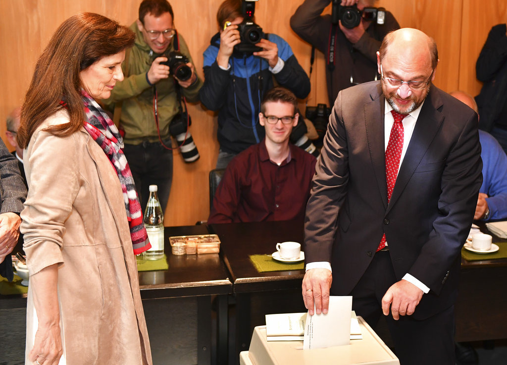 Martin Schulz, top candidate and chairman of the Social Democratic Party, is watched by his wife Inge, left, as he casts his vote in the German parliament election in Wuerselen, Germany, Sunday, Sept. 24, 2017. Schulz is challenging Chancellor Angela Merkel who is widely expected to win a fourth term in office as Germans go to the polls. (AP Photo/Geert Vanden Wijngaert)