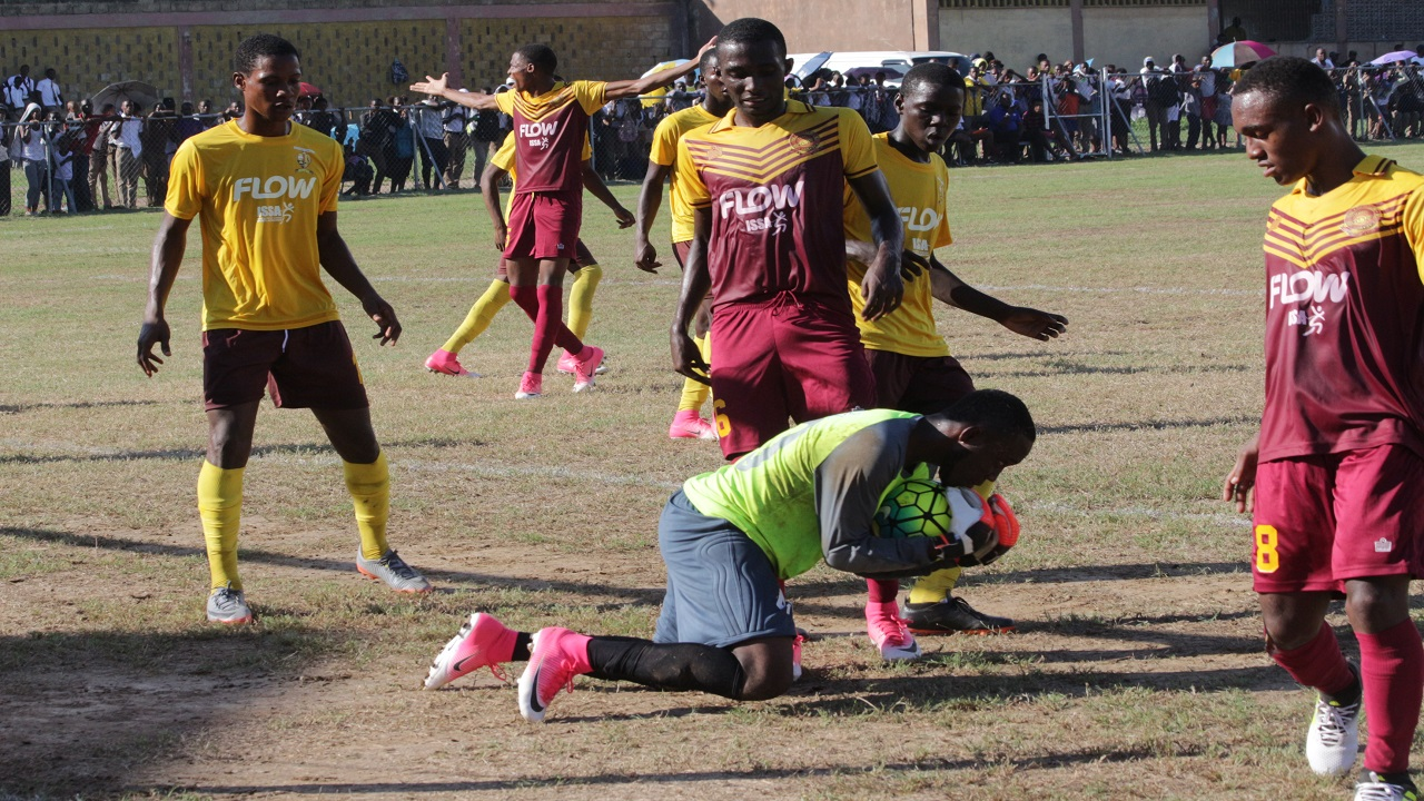 Wolmer's and Haile Selassie players look on as the latter's custodian holds on to the football in their Manning Cup match last week.