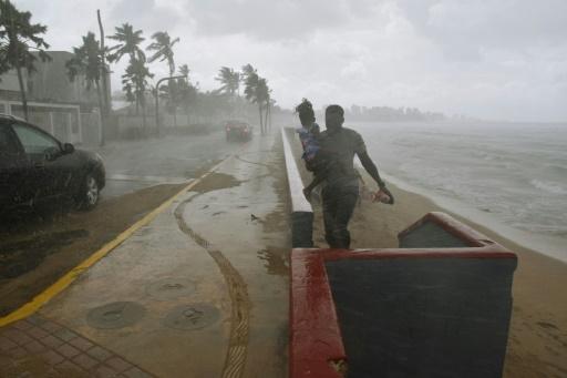 Un homme portant sa fille court pour échapper à la pluie et aux rafales de vent à l'approche de l'ouragan Maria, le 19 septembre 2017 à San Juan, à Porto Rico