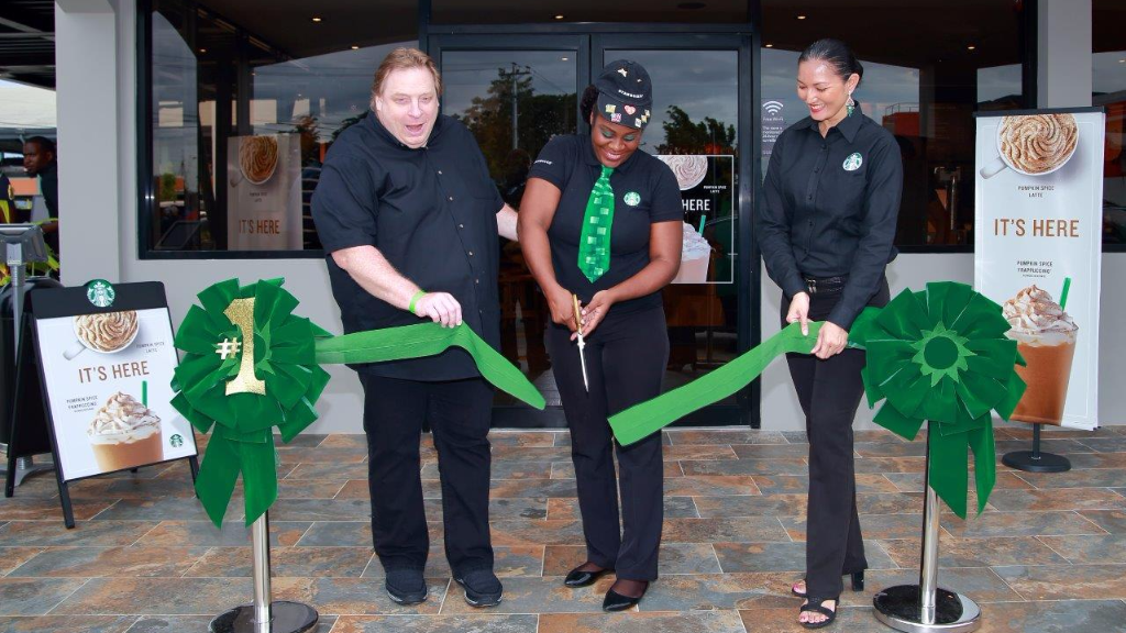 Photo: CEO, Charles Pashley, Store Manager, Pearl Skinner and VP, Starbucks, Deborah Benjamin cuts the ribbon at the Friends & Family opening of Starbucks Munroe Road, Chaguanas