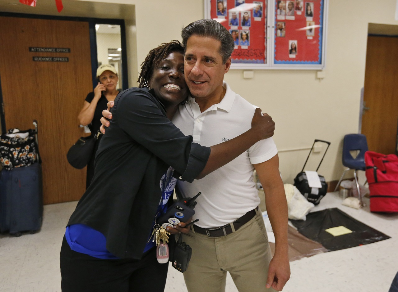 Miami-Dade County public school principal Tonya Dillard, left, gives county school superintendent Alberto Carvalho a hug as he visits a Red Cross shelter set up at North Miami Beach Senior High School, Friday, Sept. 8, 2017 in North Miami Beach, Fla.
