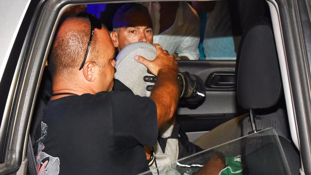 Italian police escort a teenager, at center with his head covered, in the police headquarters in Rimini, Italy Saturday Sept. 2, 2017. Two Moroccan teenagers suspected of being among four males who gang raped a Polish tourist and beat her companion unconscious on an Italian resort beach were identified at a police station Saturday by a Peruvian woman who reported being raped by the same gang shortly after the first attack, Italian media reported. (Manuel Migliorini/ANSA via AP)
