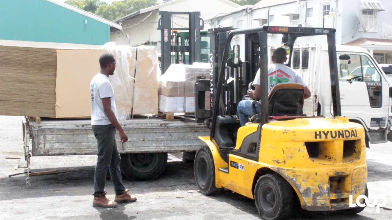 Employees of H&B Hardware loading a truck with building supplies for shipment to Dominica.