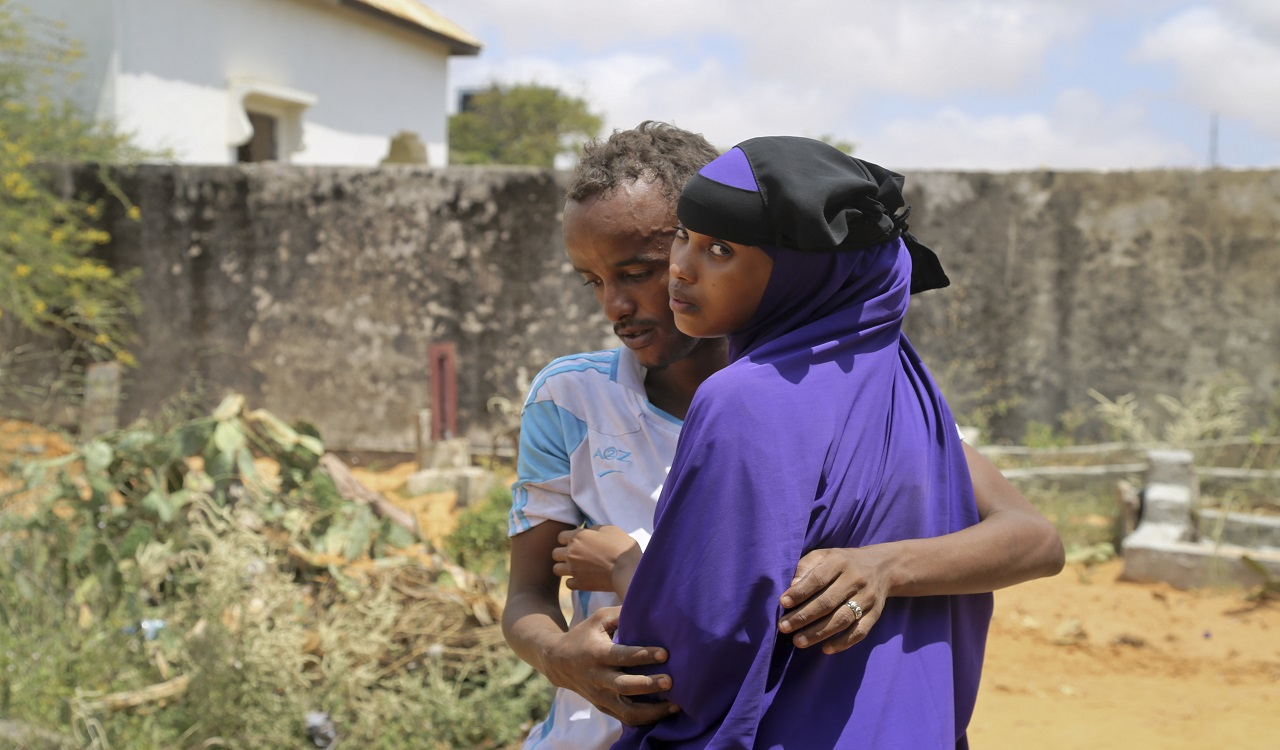 Zakariye Abdirisaq, left, who lost both his father and aunt in the bombing, is comforted by his cousin as they stand next to his father's grave, at a cemetery in Mogadishu, Somalia Tuesday, Oct. 17, 2017.