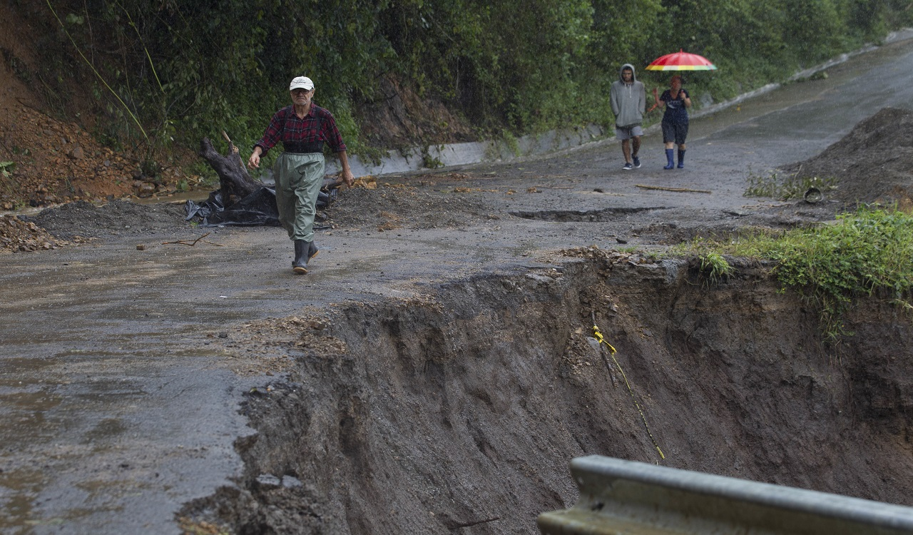 Neighbours walk under the rain past a washed out road in Alajuelita on the outskirts of San Jose, Costa Rica, Thursday, Oct. 5, 2017. Tropical Storm Nate formed off the coast of Nicaragua on Thursday and was being blamed for at least 17 deaths in Central America as it spun north toward a potential landfall on the U.S. Gulf Coast as a hurricane over the weekend.