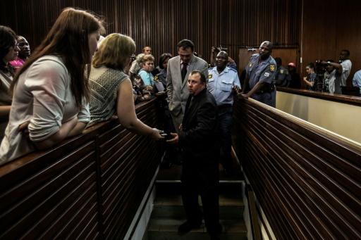 AFP / GIANLUIGI GUERCIA Willem Oosthuizen (C/G) et Theo Jackson (C/D), deux fermiers condamnés pour avoir tenté d'enfermer un homme noir dans un cercueil et menacé de le brûler, au tribunal de Middelburg, en Afrique du Sud, le 27 octobre 2017