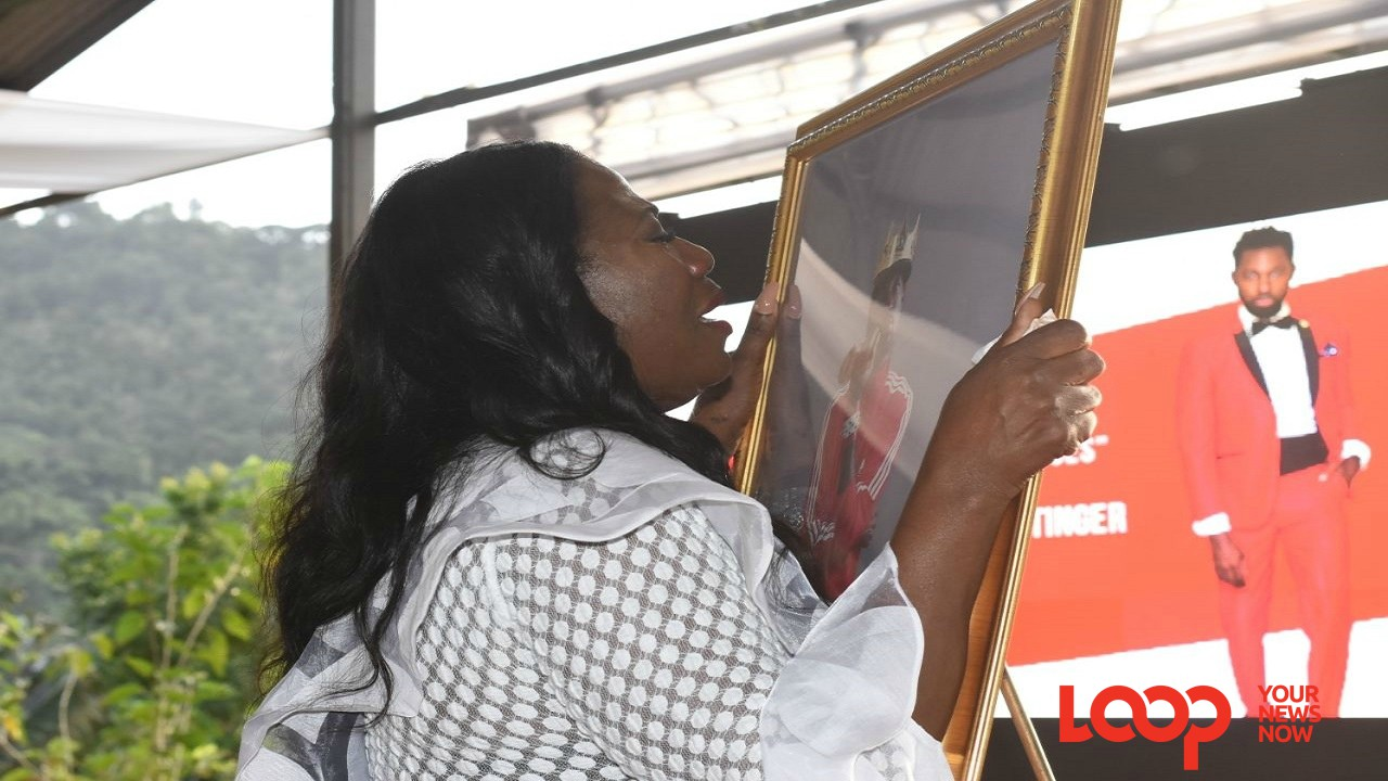 Estrie Williams, the mother of late fashion designer Dexter Pottinger, tearfully holds on to a framed photo of her son at his memorial service on Sunday. (PHOTOS: Marlon Reid)