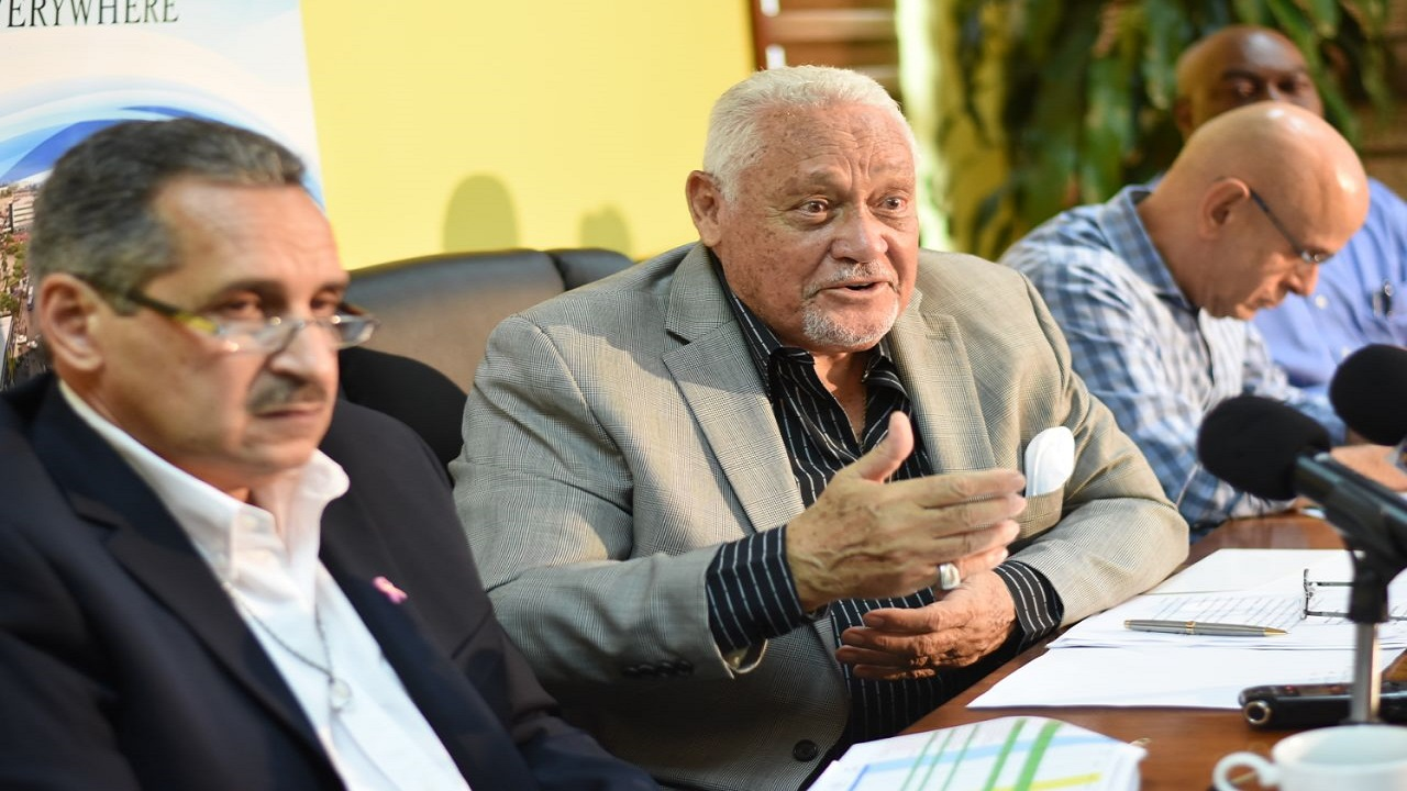 Transport Minister Mike Henry (centre) makes a point at a press conference on Friday. JUTC managing director Paul Abrahams looks on. (PHOTOS: Marlon Reid)
