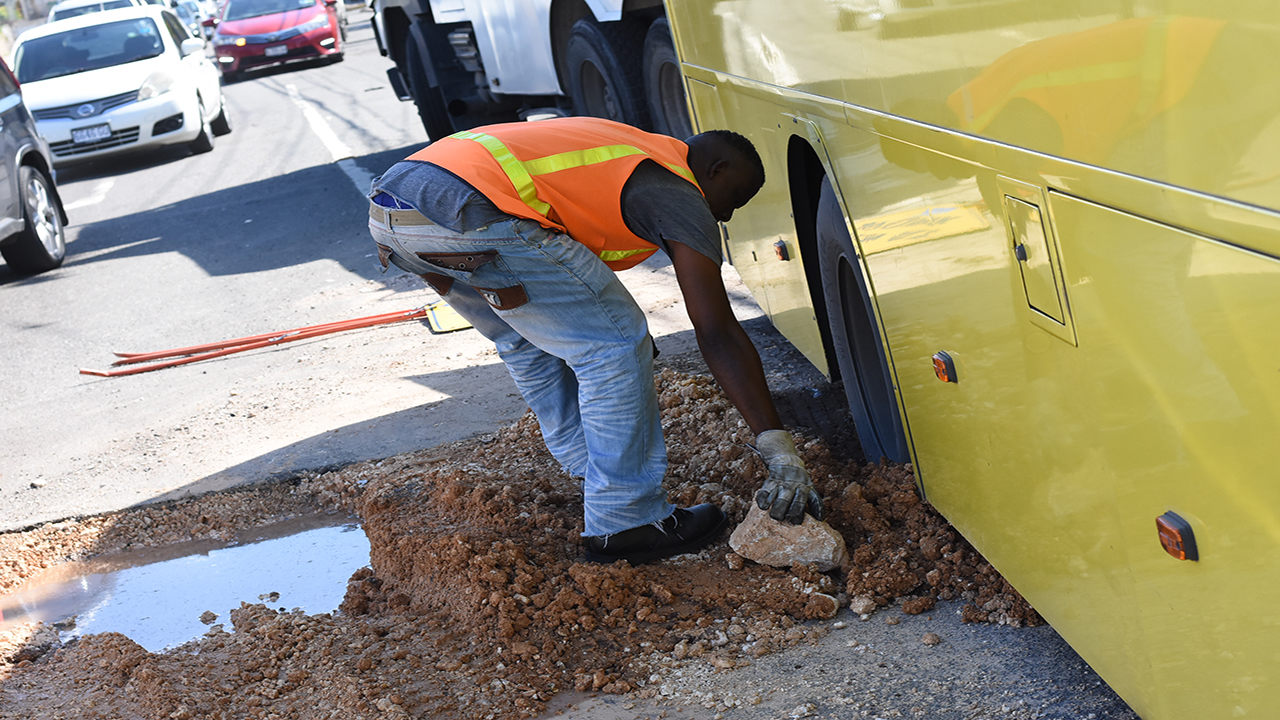 A JUTC worker attends to a bus after the vehicle became stuck along West Kings House Road in St Andrew on Tuesday morning. (PHOTOS: Marlon Reid)