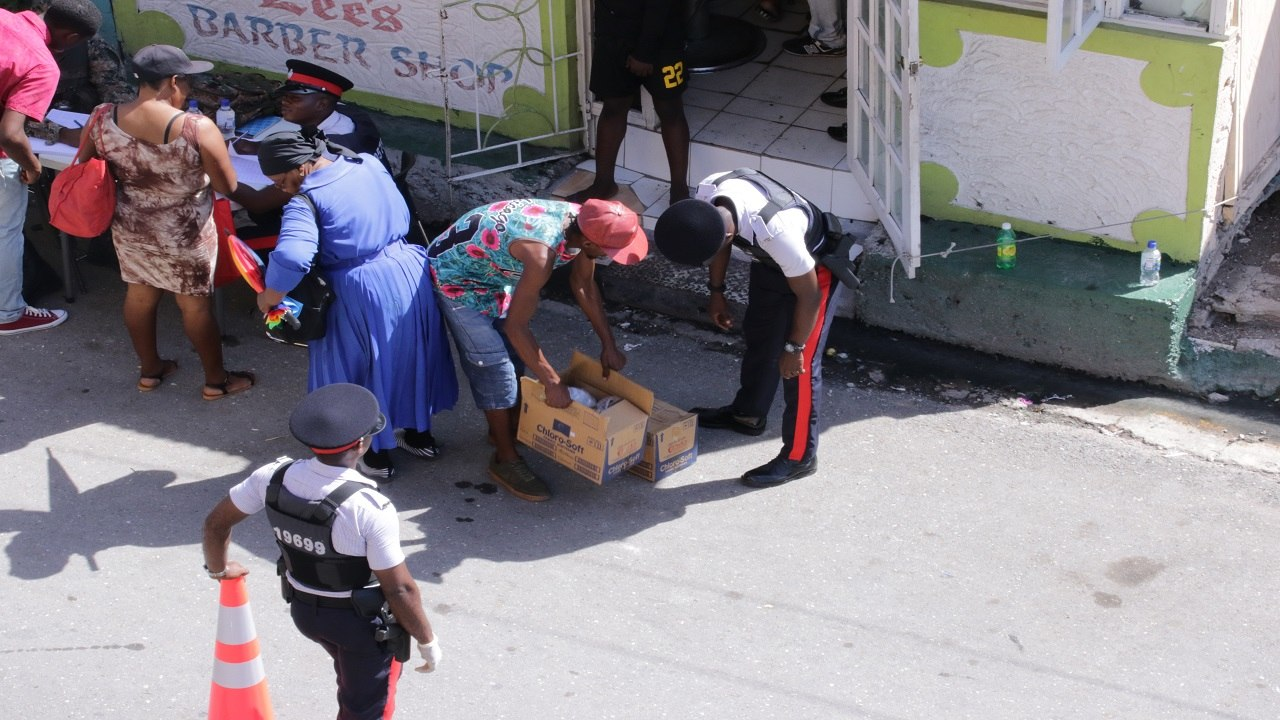 A cop searches a Denham Town resident's box while another cop looks on in the ZOSO on Tuesday.