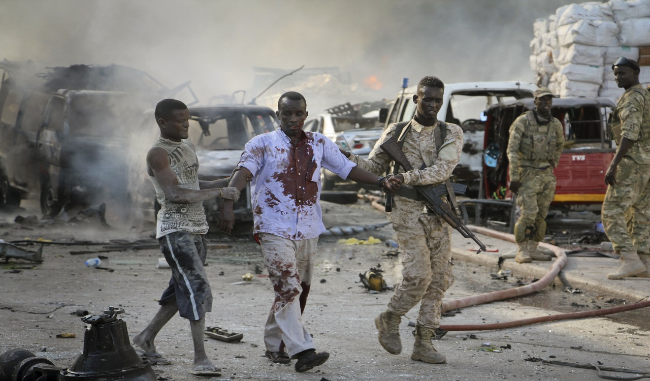 A Somali soldier helps a civilian who was wounded in a blast in the capital of Mogadishu, Somalia, Saturday, Oct. 14, 2017.