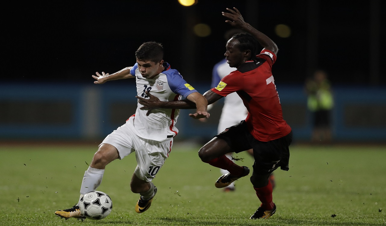 United States' Christian Pulisic, left, fight for the ball with Trinidad and Tobago's Nathan Lewis during a 2018 World Cup qualifying football match in Couva, Trinidad, Tuesday, Oct. 10, 2017.
