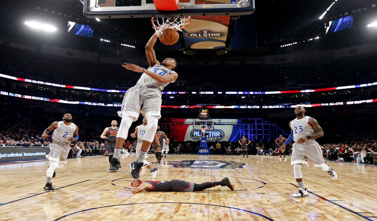 In this Feb. 20, 2017, file pool photo, Eastern Conference small forward Giannis Antetokounmpo, of the Milwaukee Bucks, dunks as Western Conference guard Stephen Curry, bottom, of the Golden State Warriors, lies on the court during the first half of the NBA All-Star basketball game in New Orleans.