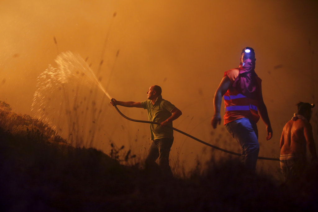 Firefighters and volunteers in Portugal try to keep the fire away from homes. (File Photo)