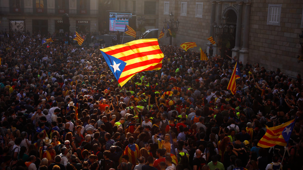"People wave ""estelada"" or pro independence flags outside the Palau Generalitat in Barcelona, Spain, after Catalonia's regional parliament passed a motion with which they say they are establishing an independent Catalan Republic, Friday, Oct. 27."