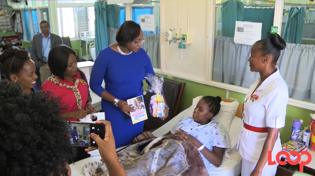 Patron for the Best for Mommy and Baby initiative, Juliet Holness hands a booklet to a new mother.