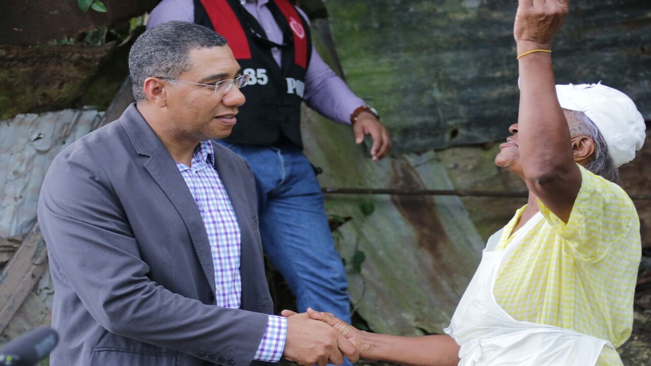 Prime Minister Andrew Holness speaks to a resident of Mount Salem following a tour of the community early last month.