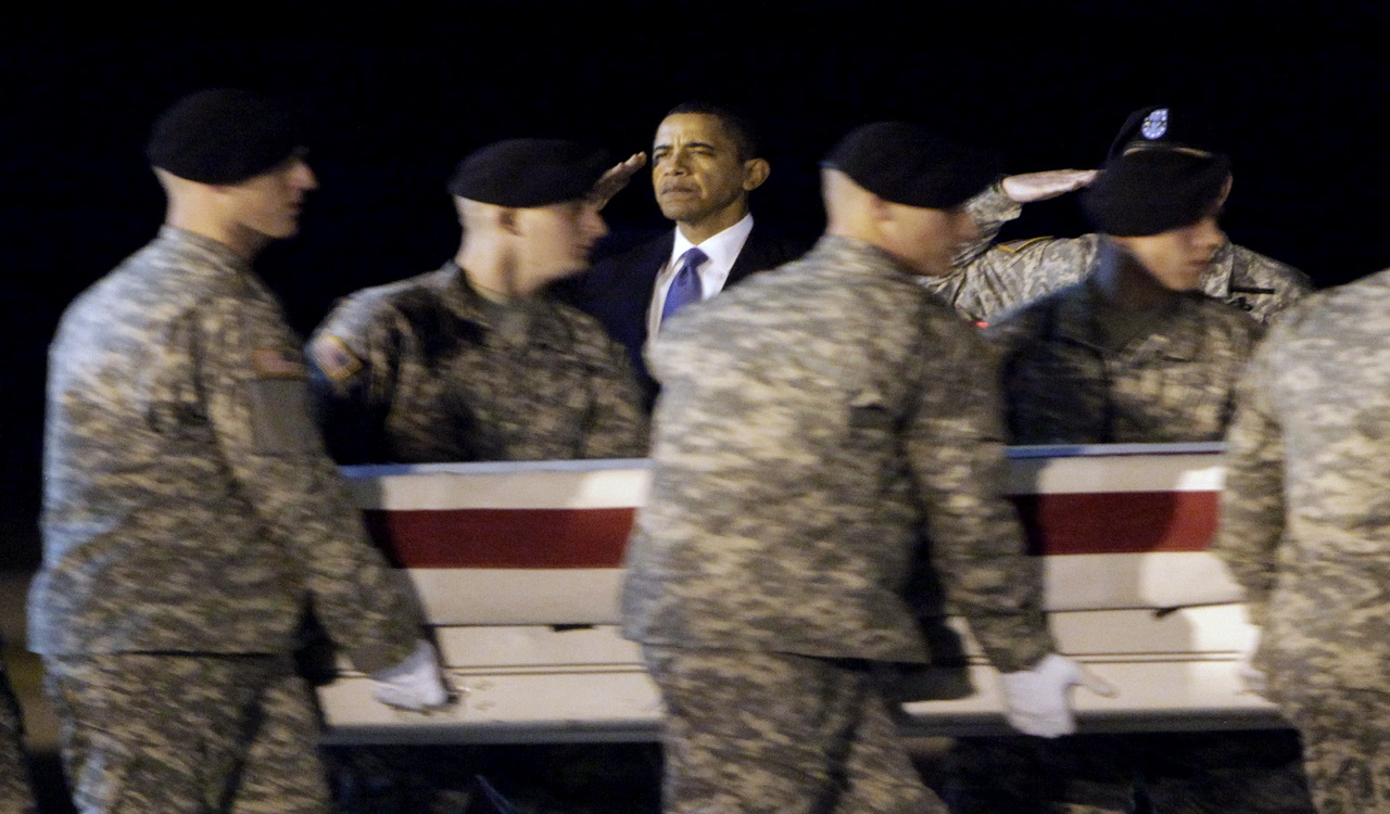 In this Oct. 29, 2009, file photo, President Barack Obama, center, salutes as an Army carry team carries the transfer case containing the remains of Sgt. Dale R. Griffin of Terre Haute, Ind., during a dignified transfer event at Dover Air Force Base, Del.